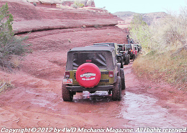 Jeep 4x4s at Moab, Utah, head up a sand canyon.