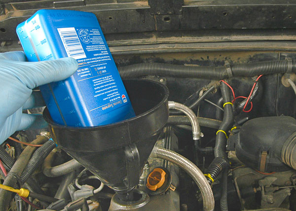 Using a funnel to fill the Jeep engine oil.