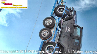 Jeep JK Wrangler hoisted into the air with a boom crane