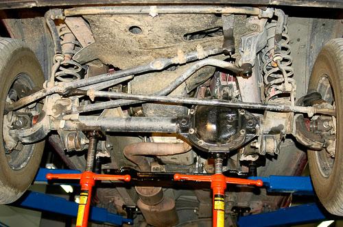 Stock XJ Cherokee suspension with vehicle on hoist.