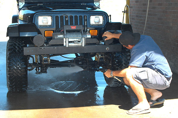 Cleaning the undercarriage of a Jeep YJ Wrangler.