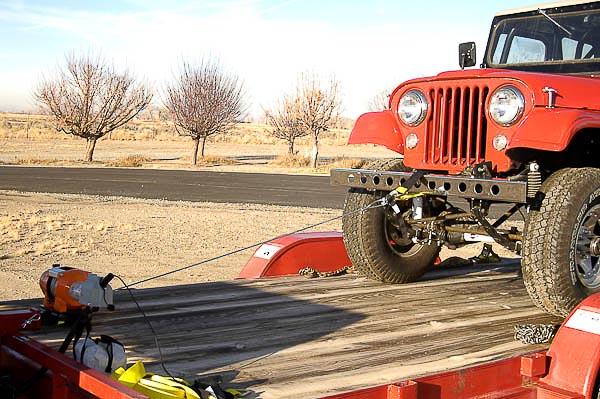 Jeep up on platform deck of trailer.