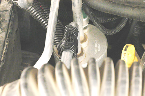 Sleeved winch cables attached to the air conditioning tube.